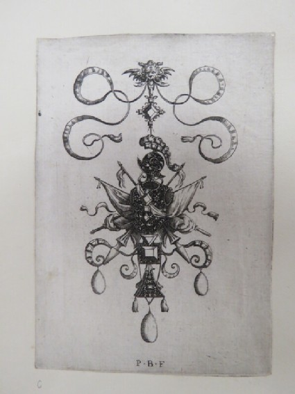 Pendant design with trophy of breast plate and helmet in centre flanked by crossed standards, swords, and lances with three drop pearls and a grotesque face at top, from Douce Ornament Prints Album I