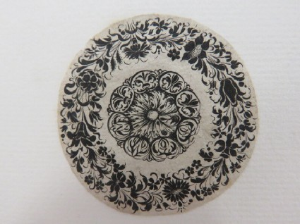 Circular medallion possibly for a box lid or watch case with flowers in centre surrounded by a flower chain composed of several varieties of flowers in blackwork, from Douce Ornament Prints Album I