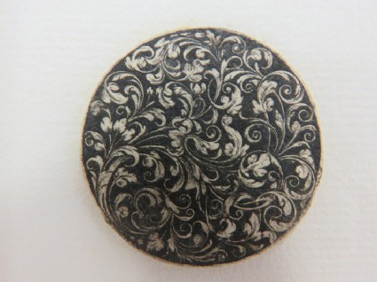 Circular medallion possibly for a box lid or watch case decorated with scrolling rinceaux foliage on a black ground, from Douce Ornament Prints Album I