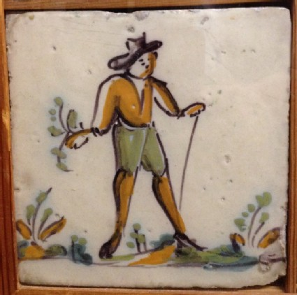 Tile with man in landscape holding stick
