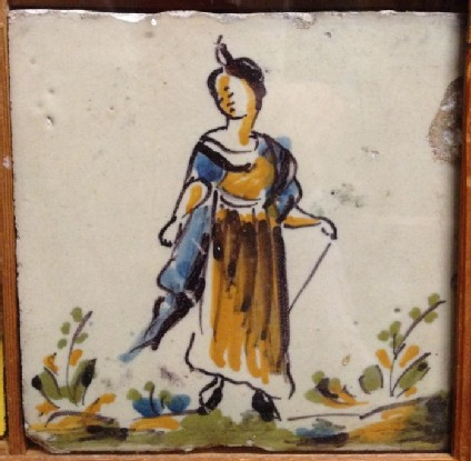 Tile with woman in landscape holding stick