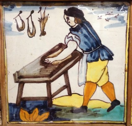 Tile with carpenter at table with tools hanging on wall