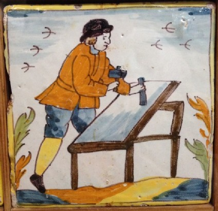 Tile with carpenter working with mallet and chisel on table in landscape