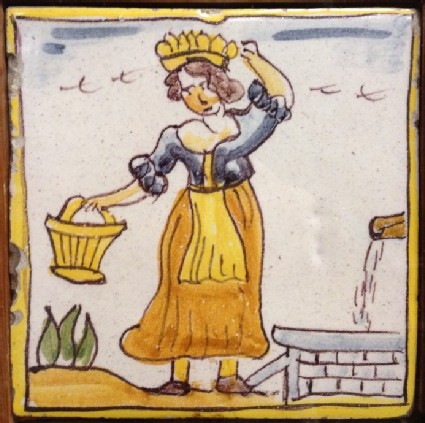 Tile with woman standing by water pump holding basket and carrying another on her head