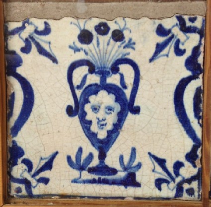 Tile with vase of flowers with face