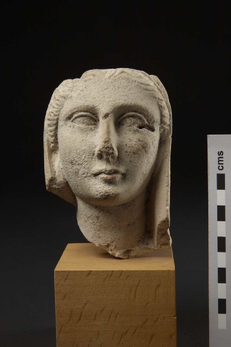 Limestone head of a female votary with veil covering the hair, fragment of votive-statuette (AN1874.337)