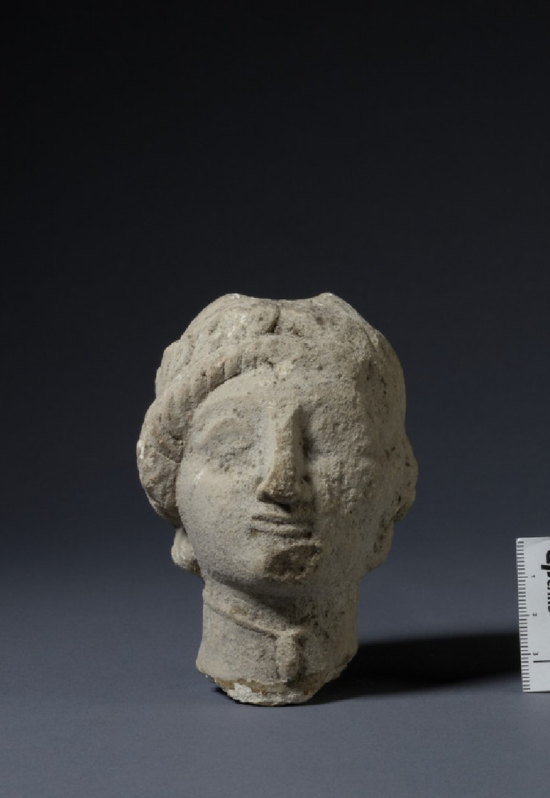 Limestone head of female votary with sakkos and wreath of leaves, fragment of votive-statuette (AN1874.338)