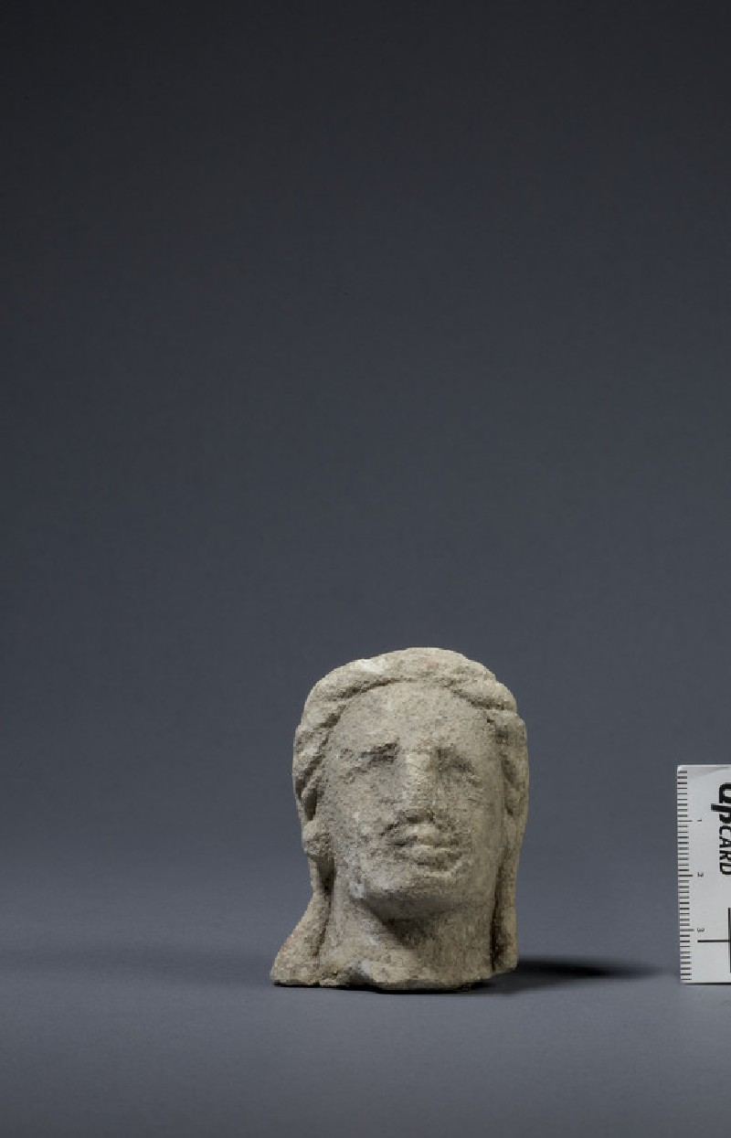 Limestone head of female votary, veiled, fragment of votive-statuette (AN1874.346)