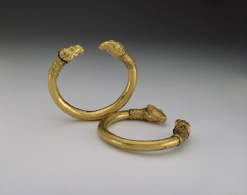 Two gold and bronze bracelets with ram's head terminals