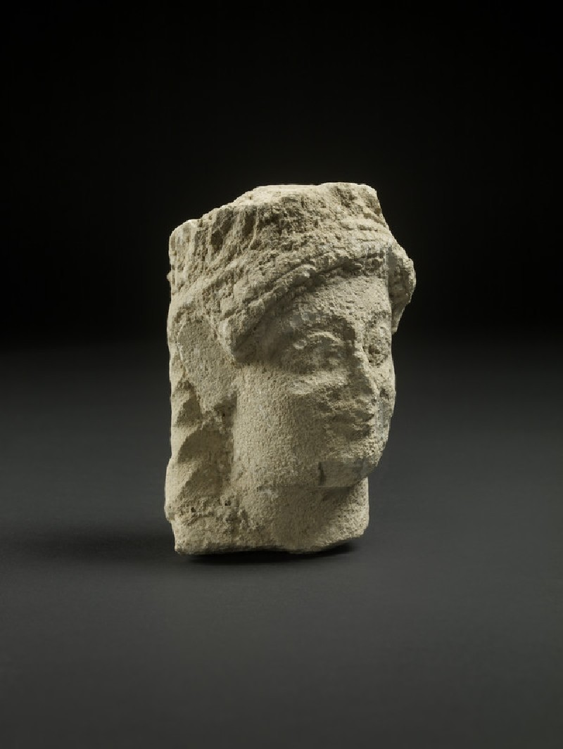 Limestone head of male or female votary with leaf-wreath and long hair at back , votive statuette