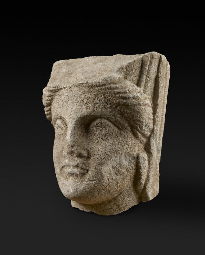 Limestone head of a a female (goddess) with turreted crown and veil  votive statuette