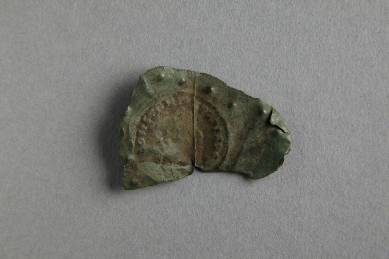 Fragment of bronze sheet imprinted with coin of Constantine I (AN1921.165)