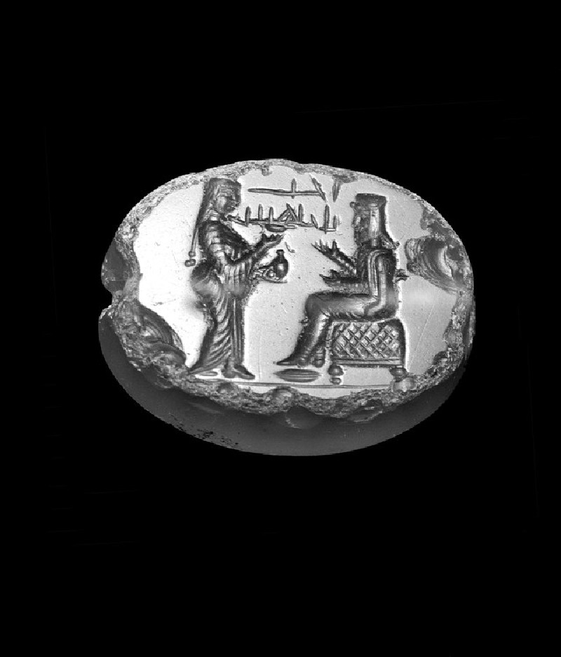 Scaraboid of blue-grey chalcedony depicting a seated Persian man (with Persian cap) approached by a woman (AN1921.2)