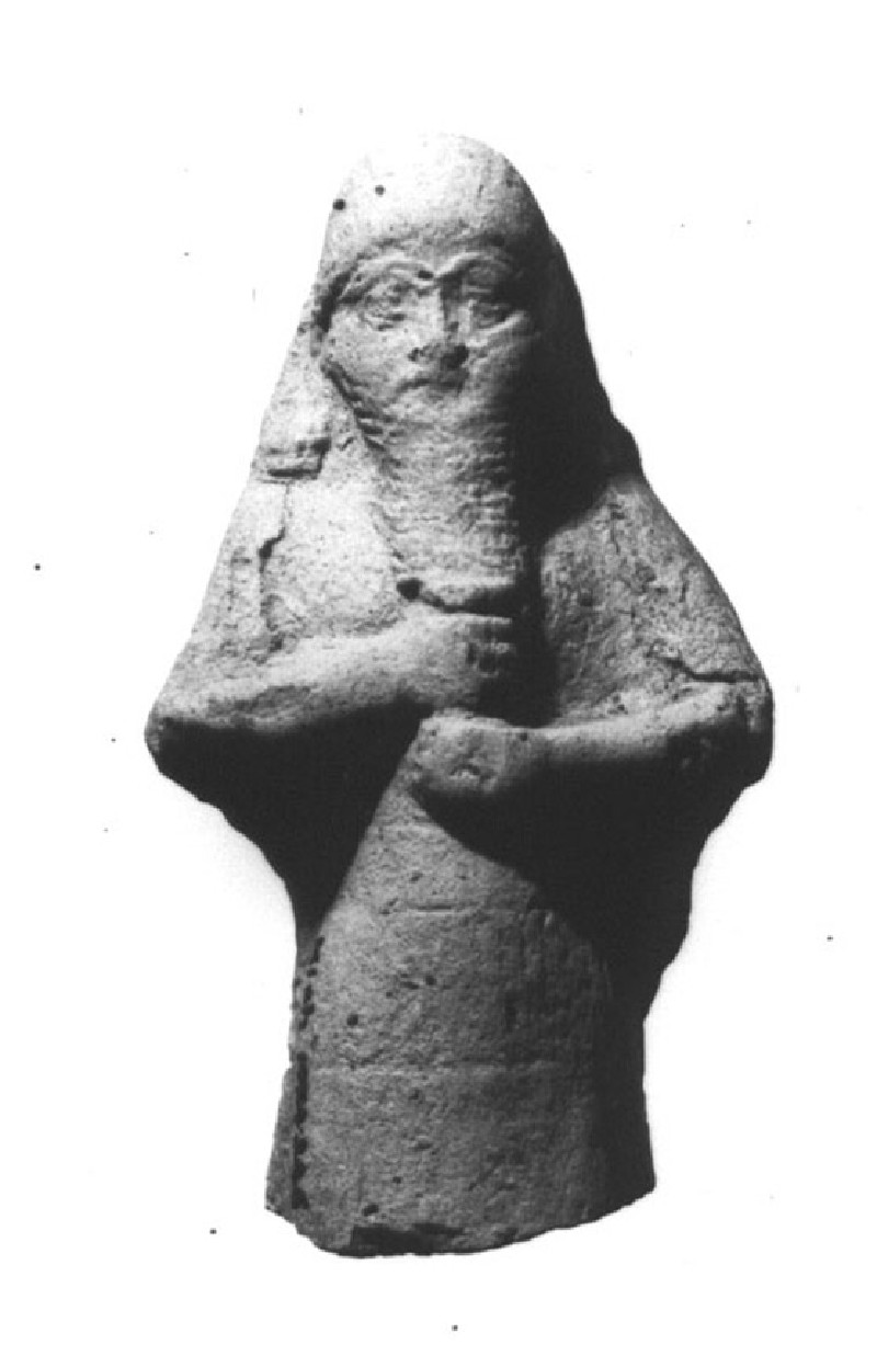 Male bearded figurine in Assyrian style holding a cup to his chest