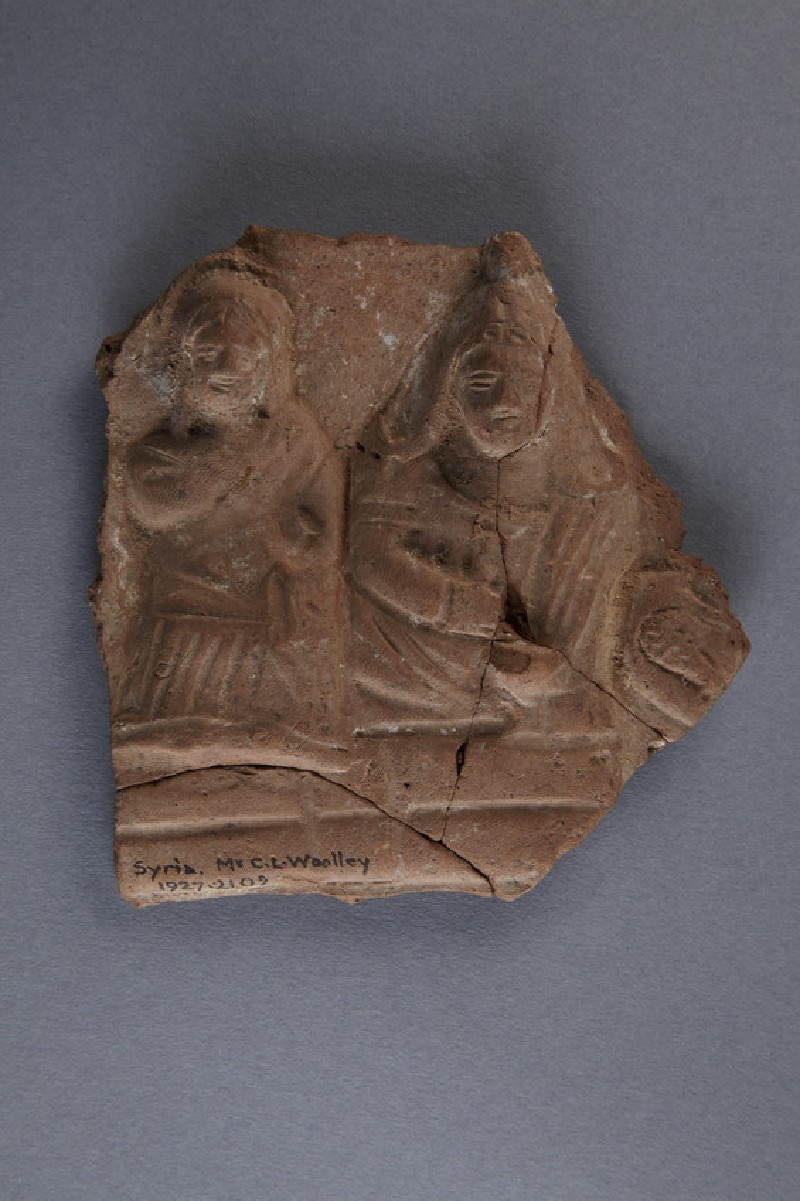 Fragment of ceramic plaque, two figures in relief: on the right, a beardless man in Phrygian attire, on the left, a woman (AN1927.2102)