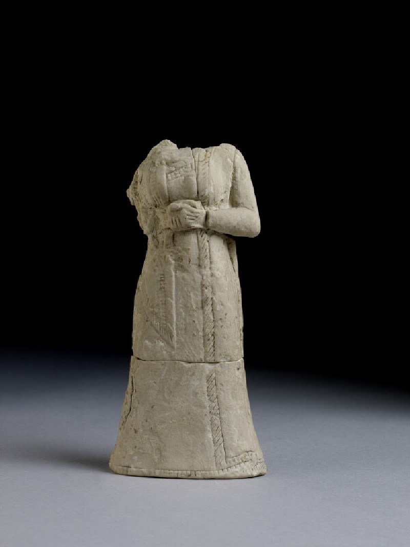 Statuette of a headless woman wearing a long robe and cloak (AN1931.51)