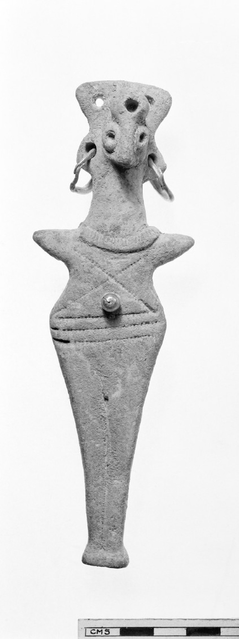 Figurine with bird-like head, flattened body, pointed arms, holes in body and head for gold decoration (AN1933.1182)