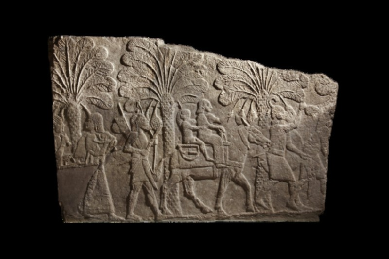 Relief depicting Babylonian campaign, woman and child captives riding on mule are escorted by Assyrian soldiers along the edge of a river, fragmentary (AN1933.1575)