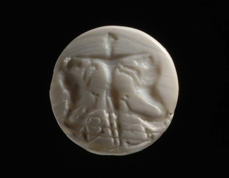 Seal depicting the 'Master of animals' a youthful god laying his hands on the heads of two attendant lions (AN1938.1054)