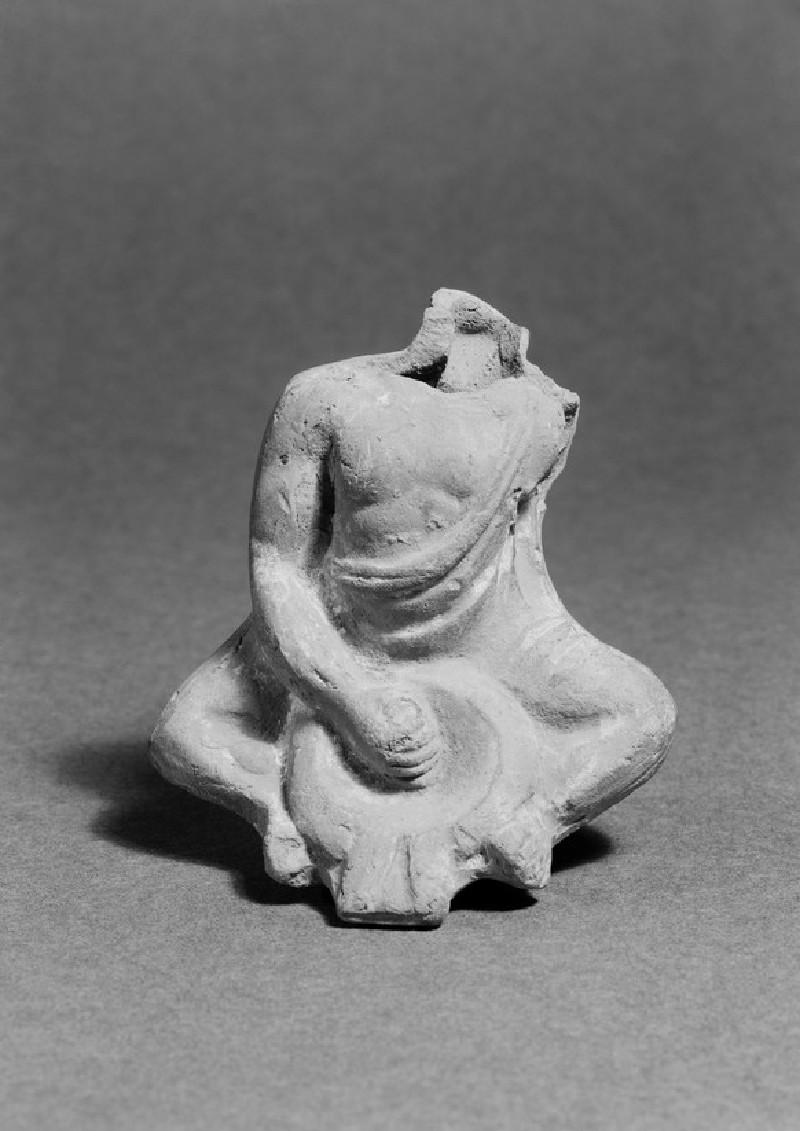Painted terracotta figurine of a slave grinding food in mortarium