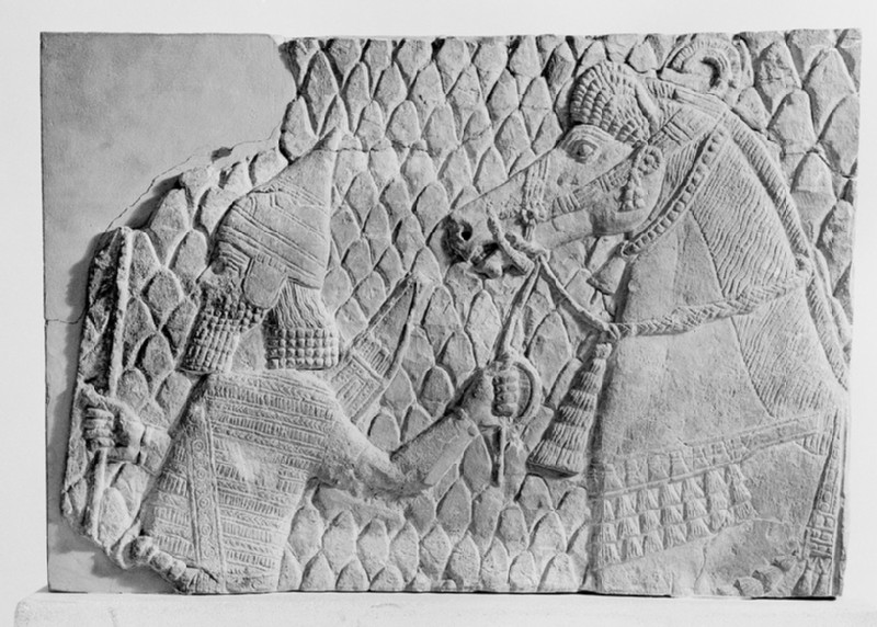 Relief, fragment depicting an Assyrian soldier holding a bow and leading a horse (AN1950.240)