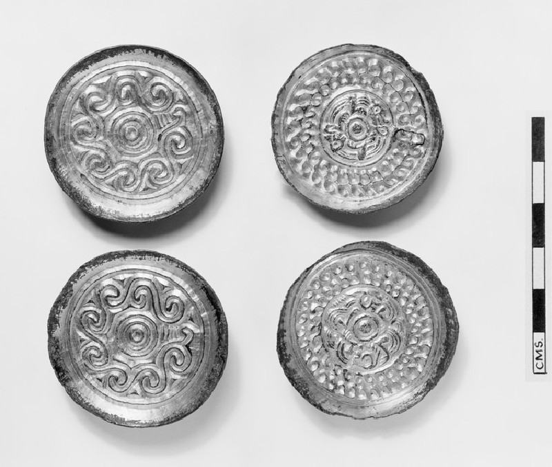 Saucer brooch with central double-ring-and-dot motif surrounded by eight irregular running spiral