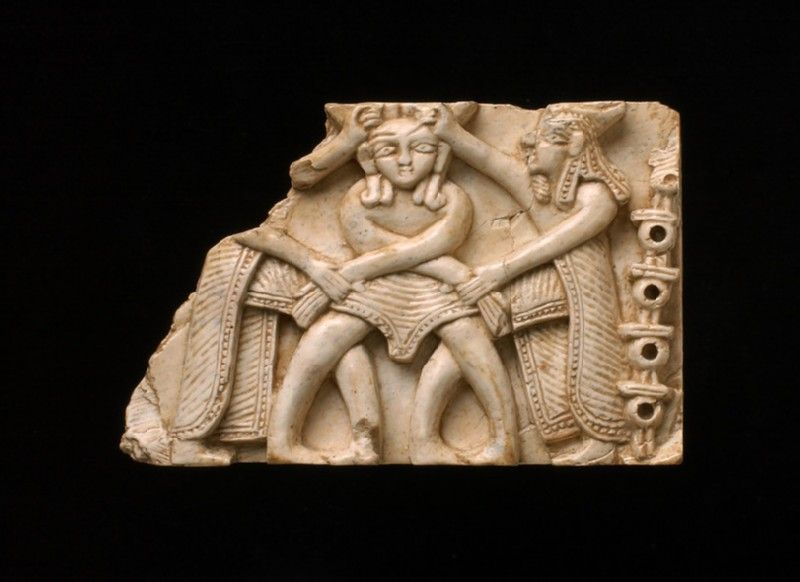 Ivory plaque, central figure has feathered headress, assailants are bewigged and crowned in Phoenician style (AN1962.307)
