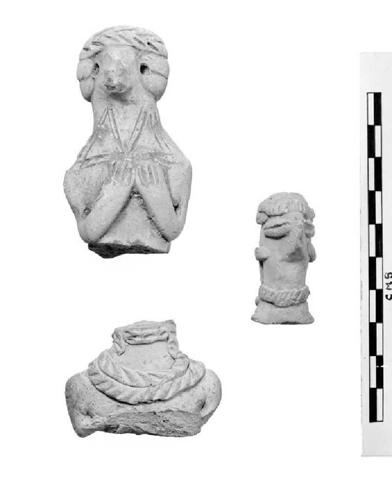 Upper part of a female figurine, hands clasped over breast