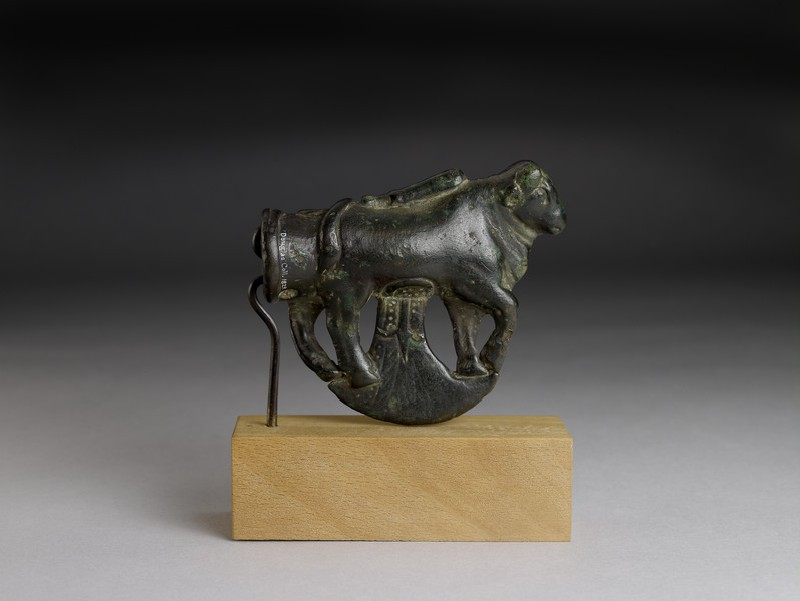 Cast bronze ceremonial axe-head: a bull, ready for sacrifice with a club lying on its back