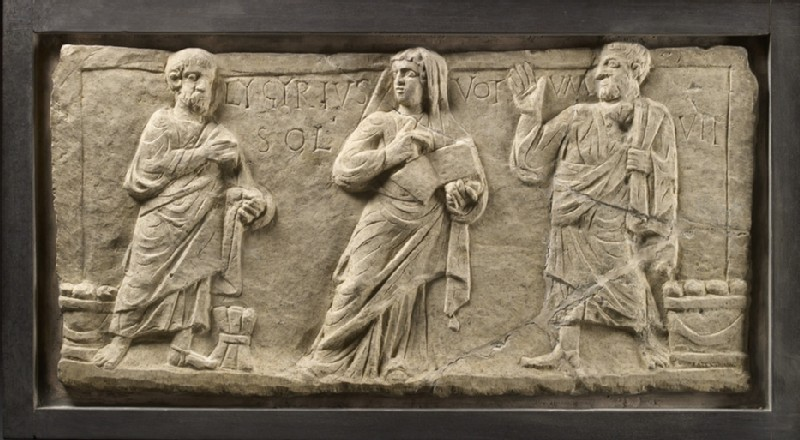 Marble relief with a woman holding an open scroll between two men with Latin inscription Lygyrius fulfilled his vow (AN2007.43)