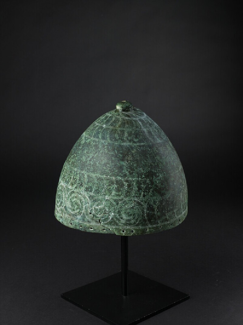 Bronze domed helmet surmounted by a knob. Decorated with punched bands of stylised boars' tusks and spirals