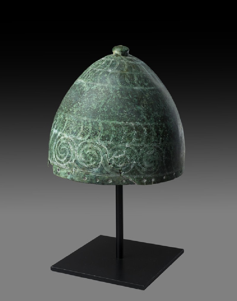 Bronze helmet. High domed form surmounted by a knob, the exterior chased with bands of stylized tusks, the lower register with an area of four linked spirals, holes around the rim for attachment