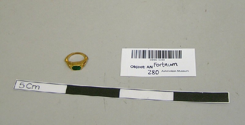 Gold ring, the deep box bezel with flat polished emerald, the openwork shoulders decorated with leaves growing out of a moulded foliate hoop (ANFortnum.FR.210, record shot)