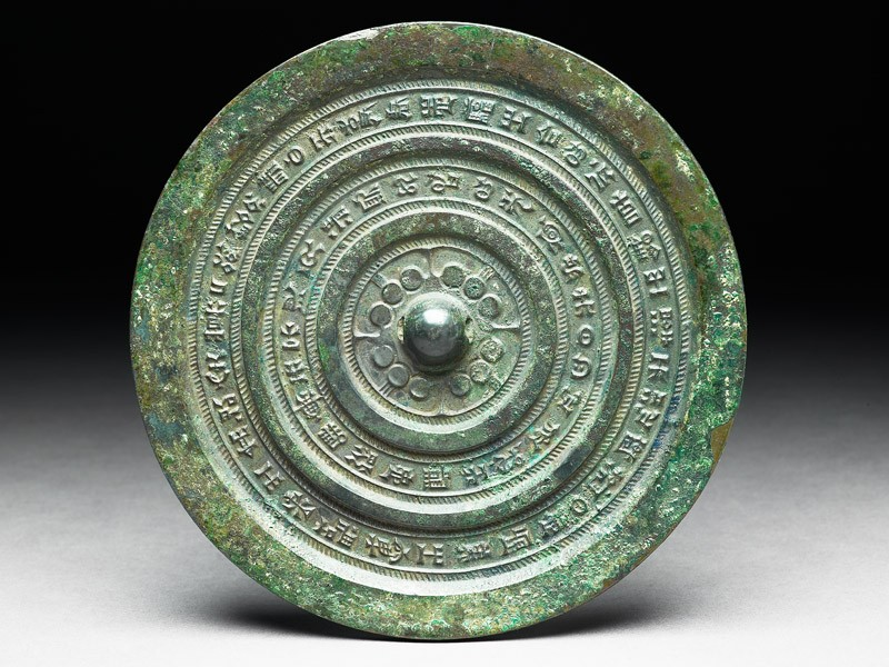 Ritual mirror with inscription between diagonally hatched bands (front             )