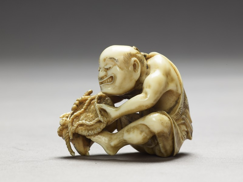 Netsuke in the form of a man making a mat