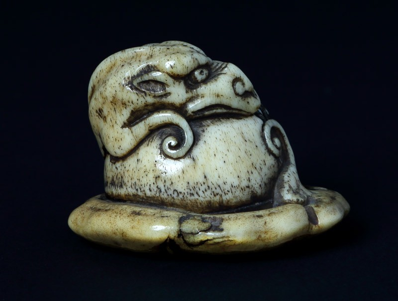 Netsuke in the form of a rain dragon coiled around a mokugyō, a Buddhist percussion instrument (front             )