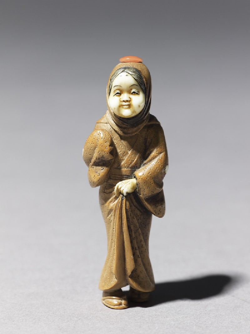 Netsuke in the form of a figure wearing a mask of Okame, a merry Shinto goddess