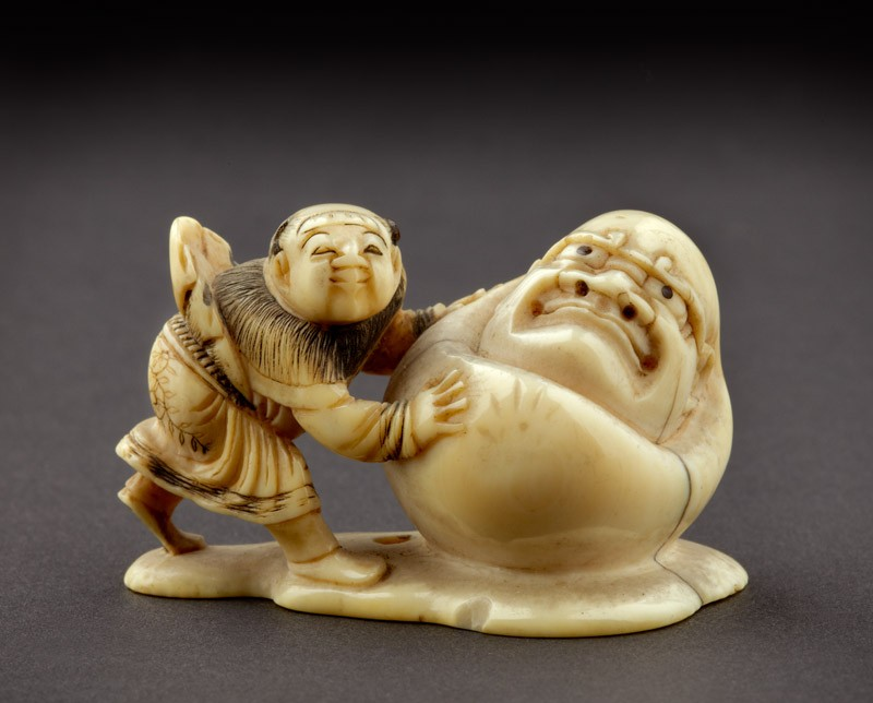 Netsuke in the form of a boy rolling a yuki daruma, or snowman (front             )