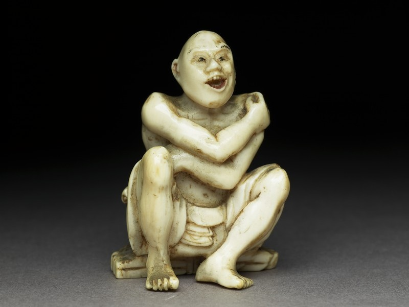 Netsuke in the form of man sitting on a mat made of twigs washing himself. He has a ladle in his left hand (EA1957.72, front           )
