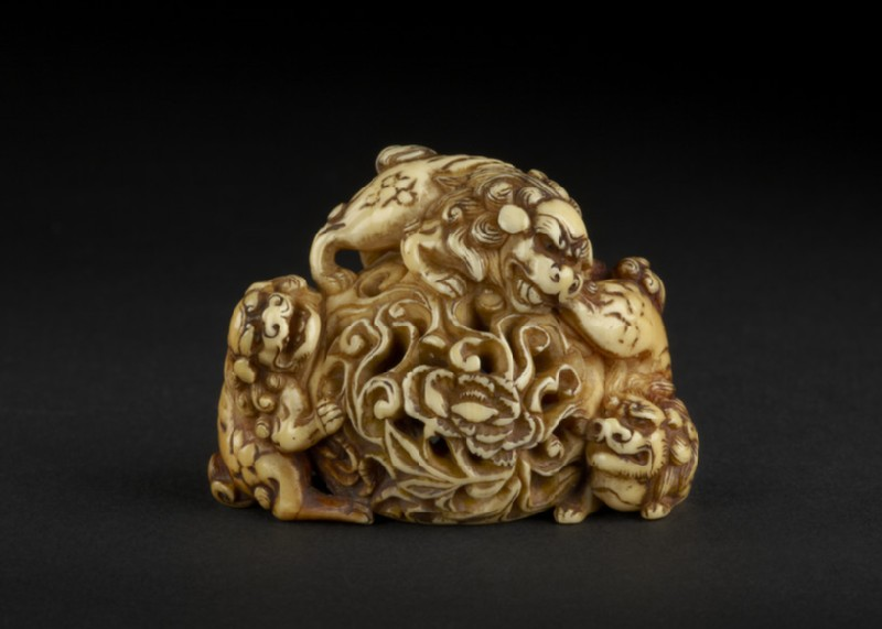 Netsuke in the form of three shishi playing on a rock