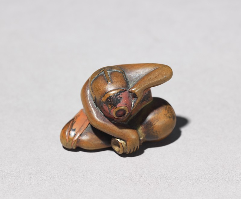 Netsuke in the form of a seated man drinking sake, holding a sake flask