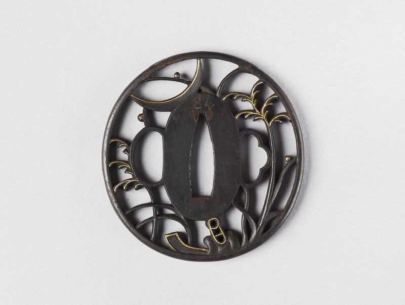Round tsuba with design of grass and a stirrup under a crescent moon