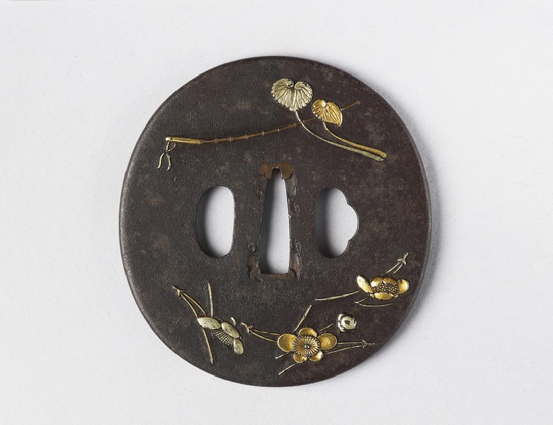 Round tsuba with design of pines needles, leaves, blossom and bamboo crop