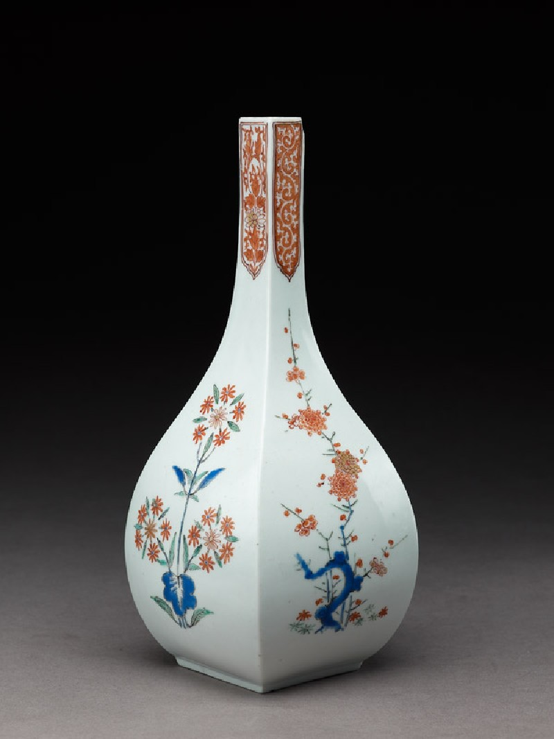 Squared bottle with prunus and formal daisy plants (side            )