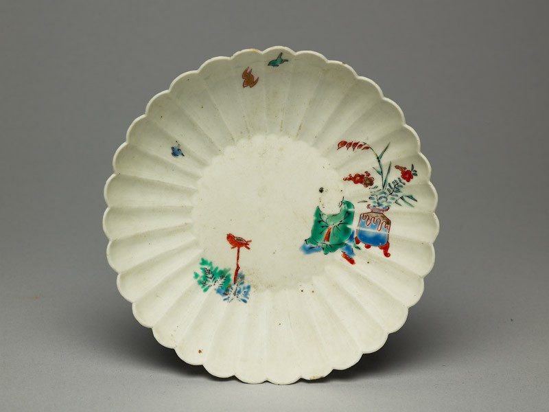 Fluted saucer depicting a boy, probably trying to catch a bird