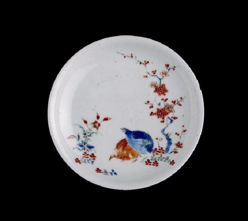 Saucer with two quails under prunus tree