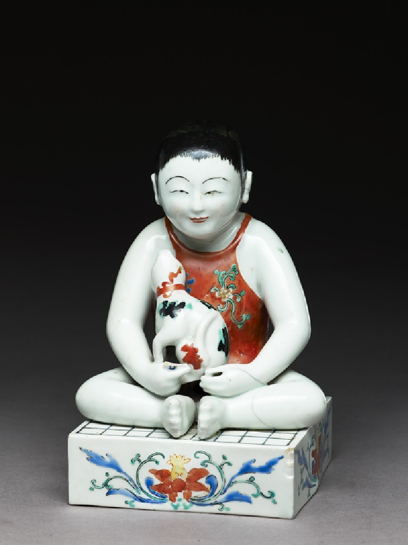 Figure of a boy seated on a shogi, or chess board