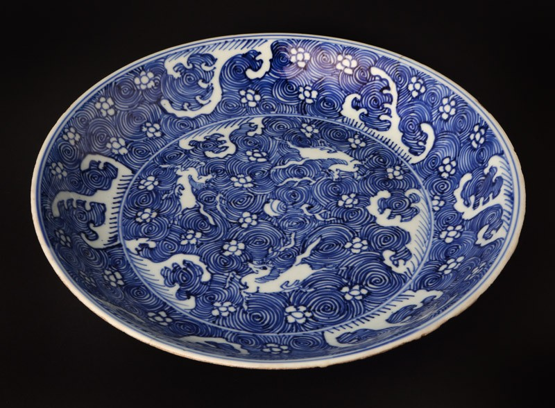 Blue-and-white dish with horses amid waves