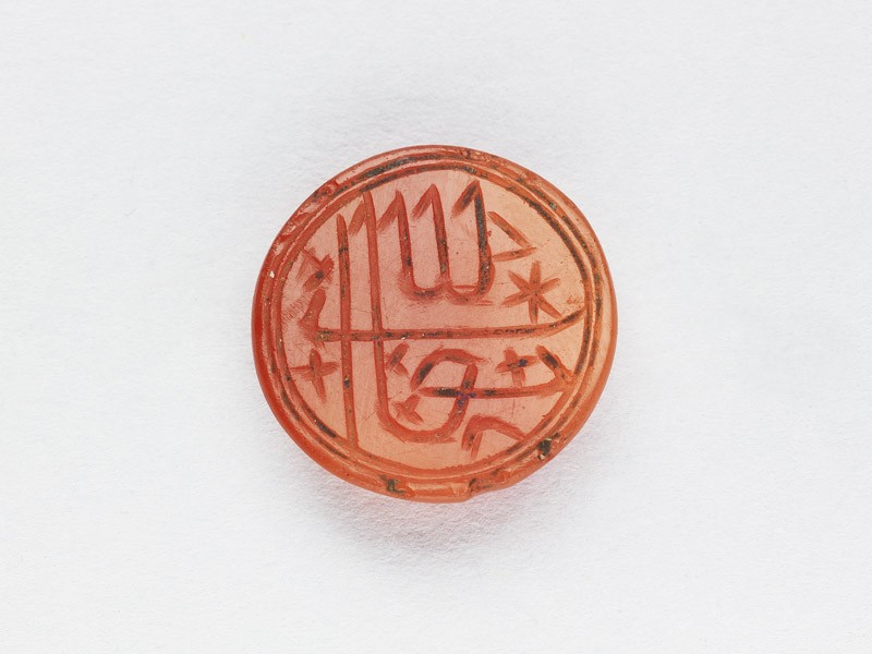 Circular bezel seal with inscription in cursive script and star decoration