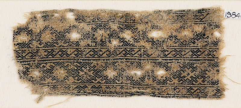 Textile fragment with linked diamond-shapes and interlaced crosses (front            )